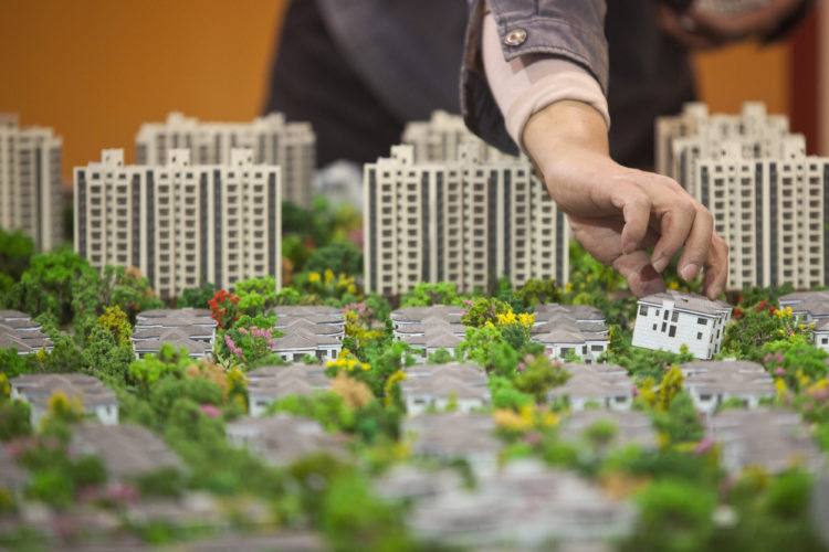 A worker installs models in preparation for a real estate exhibition in Shanghai March 14, 2013. China began 2013 with the same old economic model. Growth for the first two months of the year was driven mainly by exports and real estate. The increase in construction appears to have been fuelled by credit. The current trajectory can continue only by pumping ever more leverage, and risk, into the system. REUTER/Aly Song  (CHINA - Tags: BUSINESS REAL ESTATE) - RTR3EYWL